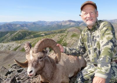 Hunter in the mountains of Magadan with his trophy, Kulu Safaris